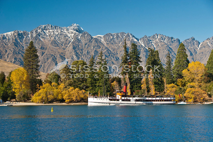 The TSS Earnslaw steams past Queenstown Gardens and the Remarkables Mountains, Central Otago, South Island, New Zealand.