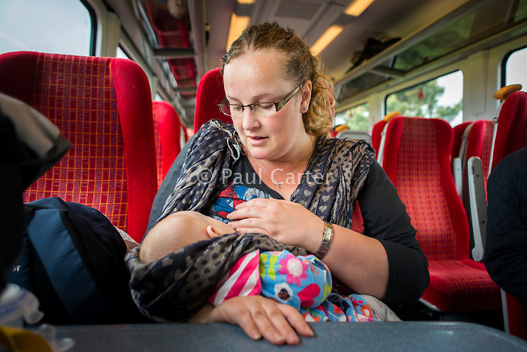 A woman breastfeeds her 14 week old baby on a train.<br /> <br /> Image from the breastfeeding collection of the &quot;We Do It In Public&quot; documentary photography picture library project: <br />  www.breastfeedinginpublic.co.uk<br /> <br /> <br /> Dorset, England, UK<br /> 20/03/2013<br /> <br /> &copy; Paul Carter / wdiip.co.uk
