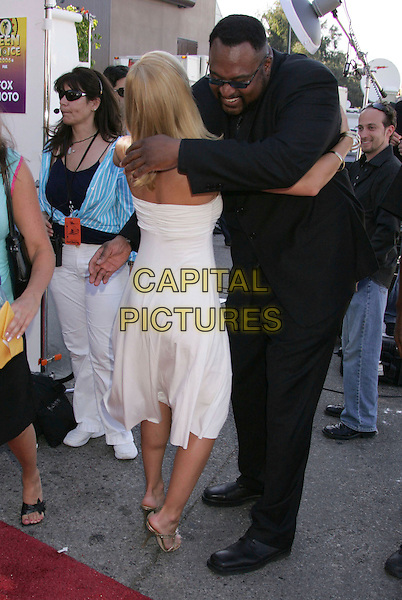 JAIME PRESSLY & GUEST.2006 Teen Choice Awards held at the Gibson Amphitheatre, Universal City, California, USA..August 20th, 2006.Ref: ADM/RE.full length white dress hug embrace back behind rear gesture black suit.www.capitalpictures.com.sales@capitalpictures.com.©Russ Elliot/AdMedia/Capital Pictures.