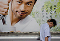 Tokyo, Japan - A tired Japanese salaryman walks past a billboard advertisement promoting refreshing beer at Shinjuku Station. Morning commuters typically spend over one hour on the train going to work. Trains are usually so packed that train platform staff have to push commuters to fit in the train so that the doors can close shut. (Photo by Yumeto Yamazaki/AFLO)