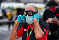 Jul 18, 2020; Clermont, Indiana, USA; John Paul DeJoria, father of NHRA funny car driver Alexis DeJoria wears goggles, a face mask and rubber gloves as he watches action during qualifying for the Summernationals at Lucas Oil Raceway. Mandatory Credit: Mark J. Rebilas-USA TODAY Sports