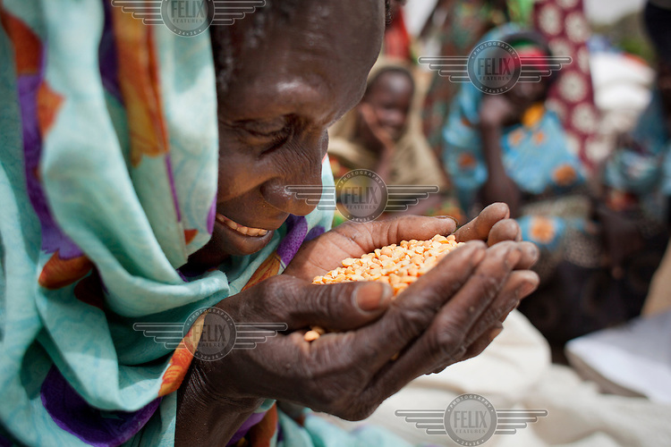 A woman closely examines a handful of grain, part of a distribution she has received from an aid agency. Lack of food has damaged her eyesight. Across the Sahel drought, exacerbated by a rise in global food prices, has left about 40% of Niger's population facing severe food insecurity. This particularly affects women and children with an estimated 127,000 children under five years old predicted to suffer from severe malnutrition during 2012.