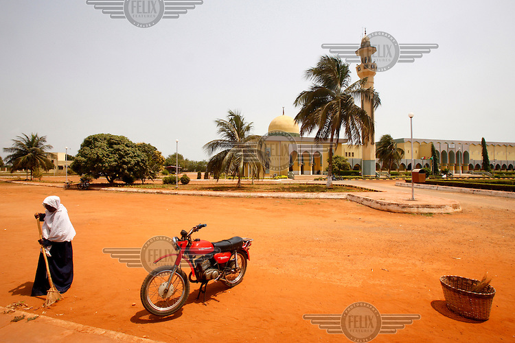 A woman sweeps the road of leaves outside the Lome Islamic Cultural Centre.