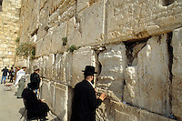Traditional men praying and prayer requests in the cracks at the famous religious Western Wall also called the Wailing Wall in Jerusalem Israel