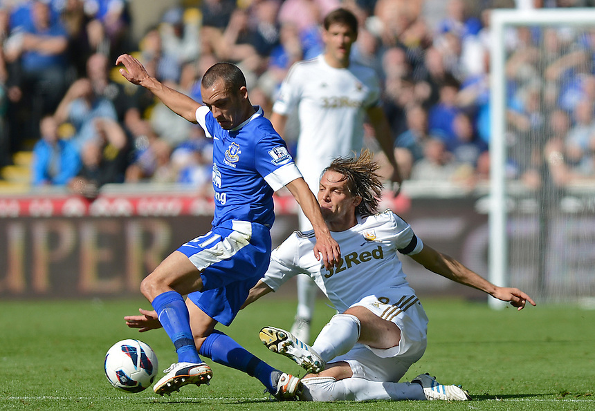 Swansea City's Michu slides in on Everton's Leon Osman ..Football - Barclays Premiership - Swansea City v Everton - Saturday 22nd September 2012 - Liberty Stadium - Swansea..
