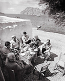 GREECE, Patmos, Diakofti, Dodecanese Island, family and friends play music and dine by the Agean Sea at Diakofti Taverna (B&W)