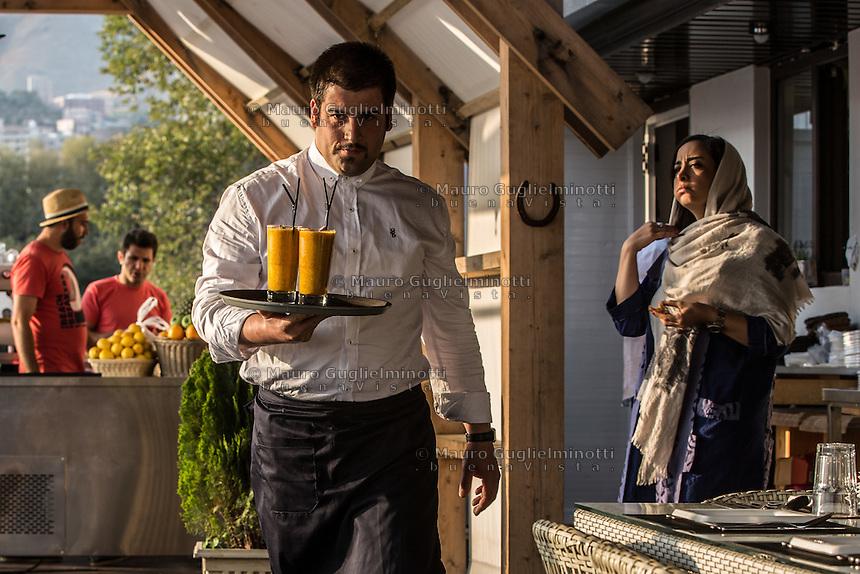 cameriere porta due succhi di frutta nel bar del golf club di Teheran, sullo sfondo donna col velo