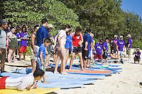 Kids learning how to surf at a charity event