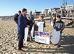 Kieran Tintle Area Manager, External Affairs for Jersey Central Power & Light hands bags out to brothers Cormac and Ciaran Lawrence, both 11 years old at the JCP&L sponsored Beach Sweep in Belmar, NJ 10/21/17.