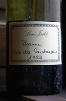 A half empty dusty old bottle with a hand written label saying Louis Jadot Beaune Clos des Couchereaux 1983 Burgundy red wine side-lit side light, closeup, Maison Louis Jadot, Beaune Côte Cote d Or Bourgogne Burgundy Burgundian France French Europe European