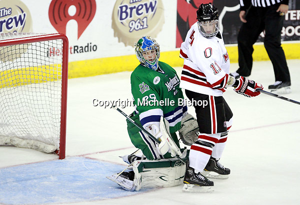 Mercyhurst goalie Max Strang and Nebraska Omaha's Jayson Megna. (Photo by Michelle Bishop) .