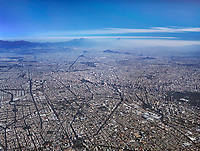 aerial overview of Mexico City toward the east with the Popōcatepētl and Iztaccihuatl volcanos in the background.