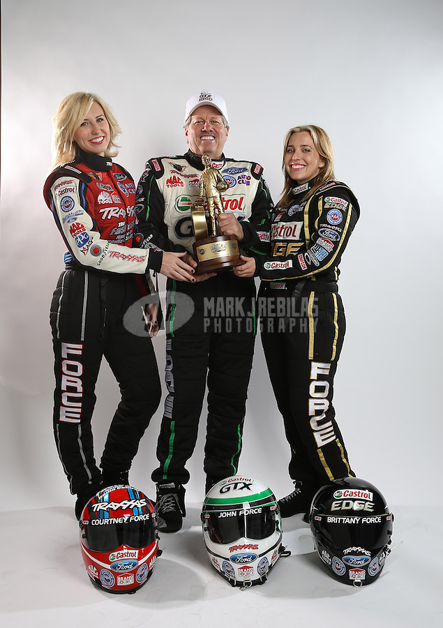 Feb. 22, 2013; Chandler, AZ, USA; NHRA funny car driver John Force (center) poses for a portrait with daughters Courtney Force (left) and Brittany Force prior to qualifying for the Arizona Nationals at Firebird International Raceway. Mandatory Credit: Mark J. Rebilas-