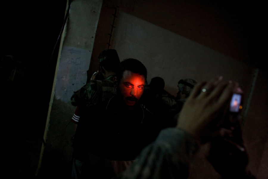 A suspect detained during a daytime raid in a darkened apartment building is photographed before being led away in central Adhamiya on Thursday April 27, 2007. The raid, which was led by Iraqi soldiers, netted two additional suspected IED triggermen.