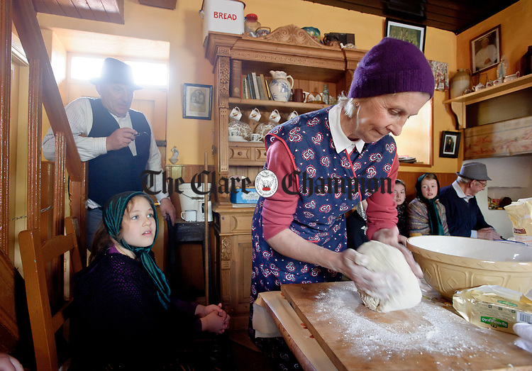 "Leila Rebai looks on as Mary Mc Mahon, ""Bean An Ti"" makes griddle bread with Paul Markham, ""Fear An Ti""  behind during a cultural visit to The Rambling House in Kilmurry Mc Mahon by pupils of Labasheeda National School. Photograph by John Kelly."