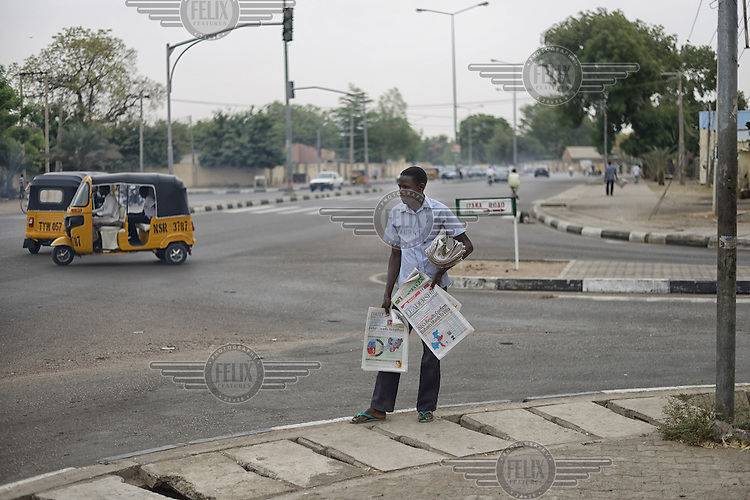 Street vendor Isa Yanusa (22), selling newspapers on a main street in Kano.  The headlines suggest a victory for the challenger Muhammadu Buhari, leader of the APC (All Progressives Congress Party) and as results continued to come in they were proved correct as Buhari was eventually declared the winner.