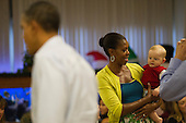 First lady Michelle Obama holds eight month old Cooper Wall Wagner as she and U.S. President Barack Obama greet members of the U.S. military and their families as they eat a Christmas Day meal at Anderson Hall mess hall at Marine Corps Base Hawaii on Sunday, December 25, 2011 in Kaneohe, Hawaii..Credit: Kent Nishimura / Pool via CNP