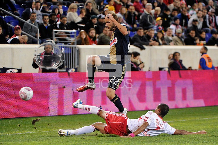 Justin Mapp (22) of the Philadelphia Union jumps over a tackle by Roy Miller (7) of the New York Red Bulls. The New York Red Bulls defeated the Philadelphia Union  1-0 during a Major League Soccer (MLS) match at Red Bull Arena in Harrison, NJ, on October 20, 2011.