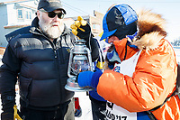 Race Marshal Mark Nordman with last place finisher and Red Lantern Award winner Cindy Abbott gives her the &quot;Widow's Lamp&quot; to extinquish signifying the last musher on the trail has reached Nome. At the finish lin  in Nome during the 2017 Iditarod on Saturday March 18, 2017.<br /> <br /> Photo by Jeff Schultz/SchultzPhoto.com  (C) 2017  ALL RIGHTS RESERVED
