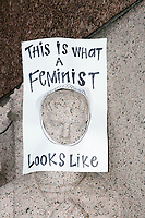 "A sign reading ""This is what a feminist looks like"" hangs on a statue as people gather in the National Mall area of Washington, DC, for the Women's March on Washington protest and demonstration in opposition to newly inaugurated President Donald Trump on Jan. 21, 2017."
