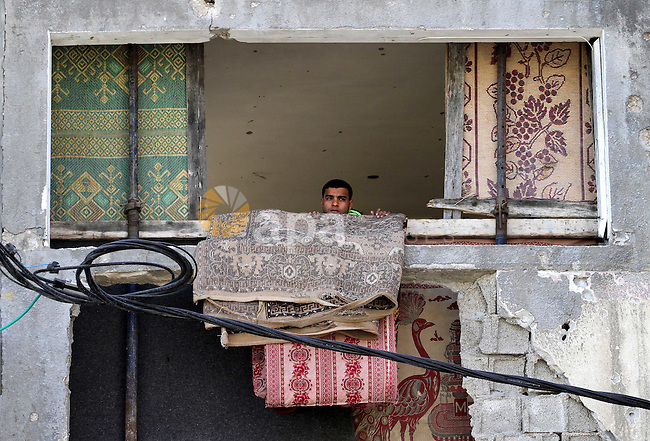 A Palestinian man looks on from his damaged house during a protest against the United Nations decision to suspend payments for Palestinians, whose houses were damaged during a 50-day war last summer, in Beit Hanoun in the northern Gaza Strip January 30, 2015. The main U.N. aid agency in the Gaza Strip said on Tuesday a lack of international funding had forced it to suspend payments to tens of thousands of Palestinians for repairs to homes damaged in last summer's war. Photo by Mohammed Asad