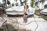 A woman stands with her children on what was once their family's home on Jinamoc Island, part of the municipality of Basey in the Philippines province of Samar that was hit hard by Typhoon Haiyan in November 2013. The storm was known locally as Yolanda. The ACT Alliance has been providing a variety of assistance to survivors here, and is planning a long-term rehabilitation program with residents which will include permanent housing.