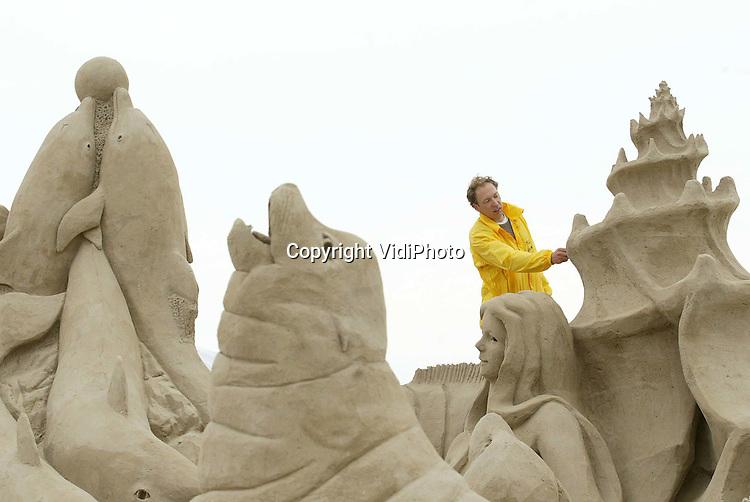 Foto: VidiPhoto..HARDERWIJK - Een zandkunstenaar legt vrijdag de laatste hand aan één van de vijf enorme sculpturen van zeezoogdieren in het Dolfinarium in Harderwijk. De zandbeelden zijn gebouwd door een team van internationale sculptuurbouwers in het kader van het vijfjarige bestaan van de De Lagune, een voor Europa uniek leefgebied voor dolfijnen, zeeleeuwen en andere zeedieren. Het is voor het eerst in de geschiedenis dat zeedieren op deze schaal in zand worden uitgebeeld.
