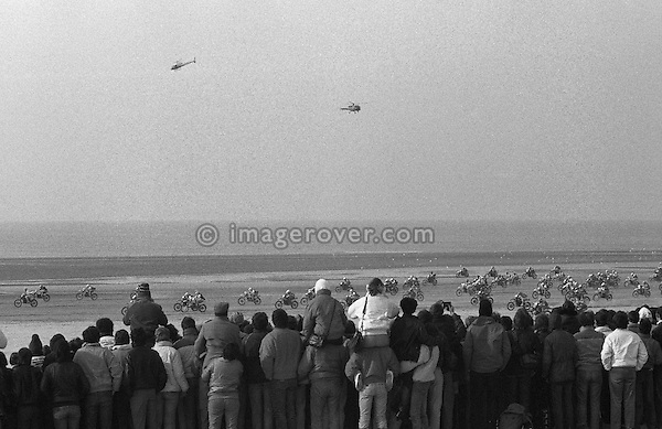 Enduro du Touquet 1986. Start along the beach. Dirt bike beach race at Le Touquet, Normandy, France. --- No releases available, but releases may not be necessary for certain uses. Automotive trademarks are the property of the trademark holder, authorization may be needed for some uses. --- Info: A thousand motorcycles take part in this mad event. The race starts along the beach, followed by a run into the sand dunes. The entry point in the dunes is most spectacular: All motorbikes have to pass through a small opening in the dunes. Once the fast professional drivers have flown through, this first passage developes into a true bottleneck with many hundreds of motorbikers trying to get through at the same time. Motorcycles are strewn all over the place. Many have fallen, others have already broken down. In the meantime, the professional riders are progressing quickly. But their riding style changes from racing full-out as soon as they are approaching the lappers from behind. Outmaneuvering them at high speeds is an art form! After three hours it's all over.....