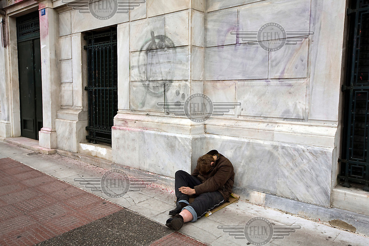A homeless man sleeps whilst begging near Syntagma Square.