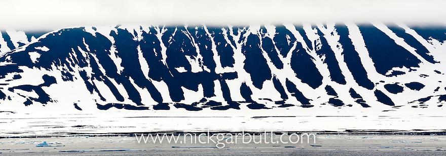 Melting snow and rock patterns on cliffs. Woodfjorden, northern Spitsbergen, Svalbard, Arctic Norway.