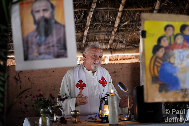 Father Mario Benedetti, a 75-year old Comboni priest from Italy, celebrates Mass in  the chapel of the Makpandu refugee camp, a ramshackle collection of huts with mud walls and thatched roofs spread through a remote section of forest 40 kilometers from Yambio, the capital of Western Equatoria State in the newly independent South Sudan. More than 3,000 people live in the camp, having fled the Democratic Republic of the Congo in 2008 when the Lord's Resistance Army started a murderous rampage through the area. In recent months the Congolese have been experiencing harassment and insults from the local population. Religious workers say the refugees want to go home to the Congo, but not until Joseph Kony and the LRA are removed. The portrait hanging in the upper left of the image is St. Daniel Comboni. Fr. Benedetti accompanied the refugees to the camp when the fled the Congo.