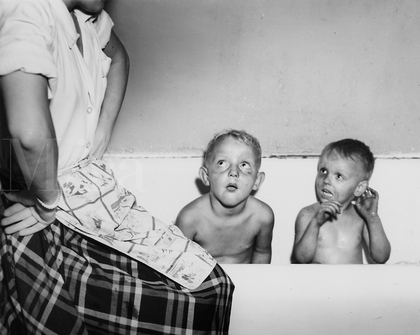 Two very dirty boys in bathtub looking up at mother. 1950's.