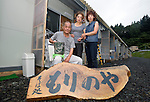 Sisters Hiroko Ninuma (R) and Miyoko Sasaki (center) and her husband Kazuyasu pose for a photo in front of their temporary home in Kamaishi, Iwate Prefecture, Japan on 02 Sept. 2011. The family's noodle restaurant was washed away by the March 11 tsunami, but the shop sign, shown in the foreground of this photo, was recovered from the rubble. Photograph: Robert Gilhooly