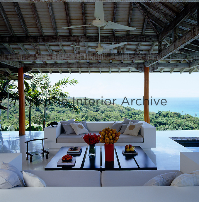 The open-air poolside living area has built-in concrete sofas and a spectacular view over the jungle towards the ocean