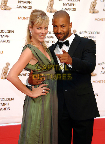 TYRON RICKETTS & GUEST.At the Golden Nymph awards ceremony during the 2008 Monte Carlo Television Festival held at Grimaldi Forum, Monte Carlo, Principality of Monaco, .June 12, 2008..half length green dress hand on hip finger pointing.CAP/TTL.©TTL/Capital Pictures