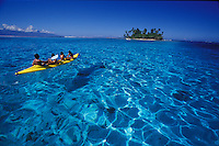 Parent and children paddling a kayak to a 'motu' islet in the clear waters of Moorea's lagoon, Tahiti, French Polynesia