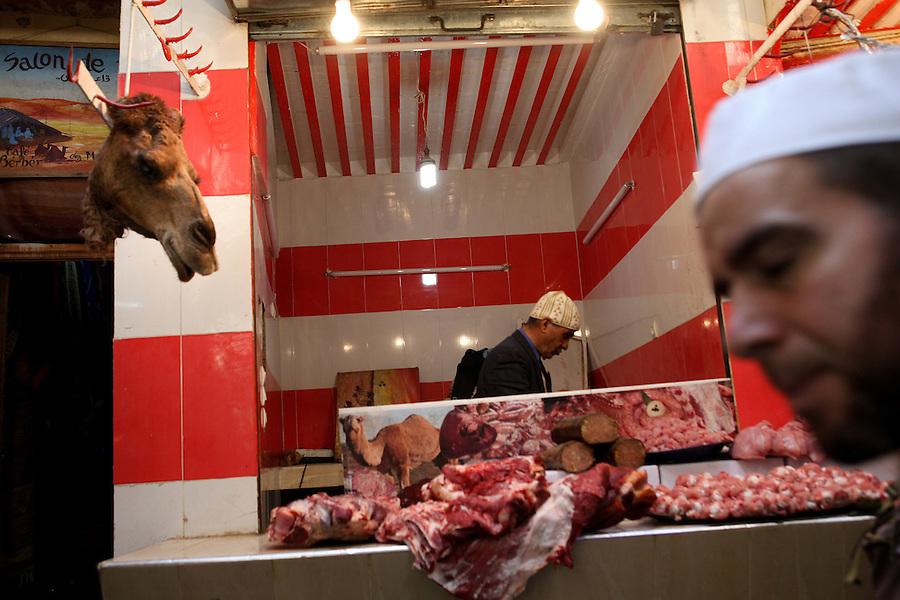A man walks past a camel head hanging outside a butcher's booth in Fez, Morocco.
