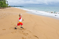 Two year old boy playing on the beach at Playa Bluff Lodge, Bocas del Toro, Colon Island, Panama