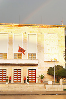 The presidential president's palace with Albanian flag and honour guard. On the boulevard Bulevardi Deshmoret e Kombit. Rainbow in the sky. Tirana capital. Albania, Balkan, Europe.