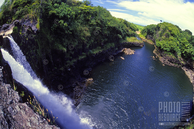 Stunning Rainbow Falls cascades down the mountain into a blue pool on the Hamakua Coast near Hilo.