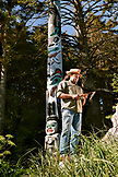 ALASKA, Sitka, Tommy Joseph a Tinglit totem pole carver stands in front of one of his carvings, Halibut Cove, Sitka Sound