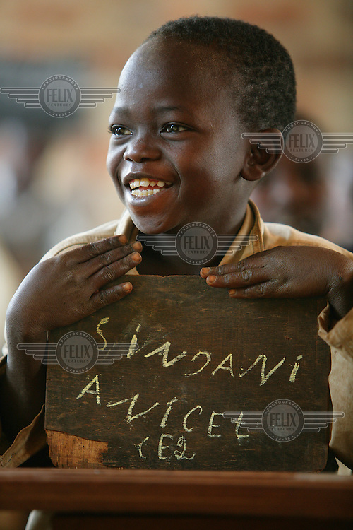 Boy in class at community school - his name is written on the slate.