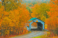 Autumn colors surround the covered bridge - Pont Des Draveurs - across the Petite rivi&egrave;re Neigette.<br />