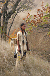 A serious male portrait of a young Native American Sioux Indian boy standing on a hill in South Dakota during the fall season
