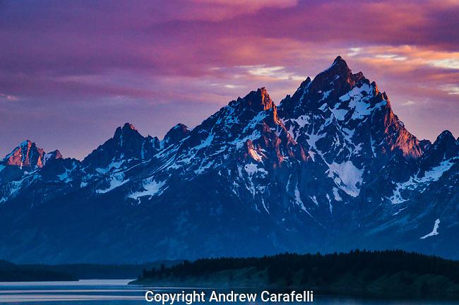 The Teton Mountains in Wyoming glow red at sunset.