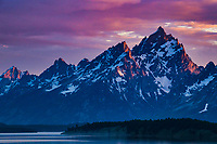 The Teton Mountains in Wyoming glow red at sunset.