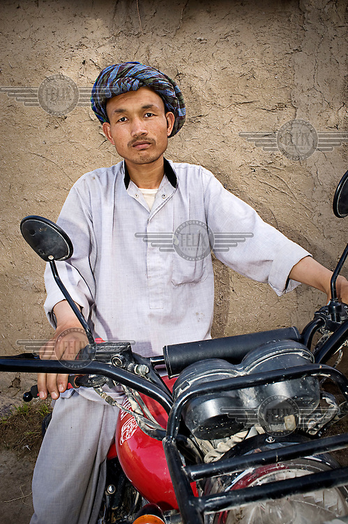 A man sits astride a motorbike.