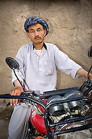 A man sits astride a motorbike.