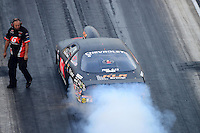 Jun. 29, 2012; Joliet, IL, USA: A crew member looks on as NHRA pro stock driver Erica Enders does a burnout during qualifying for the Route 66 Nationals at Route 66 Raceway. Mandatory Credit: Mark J. Rebilas-