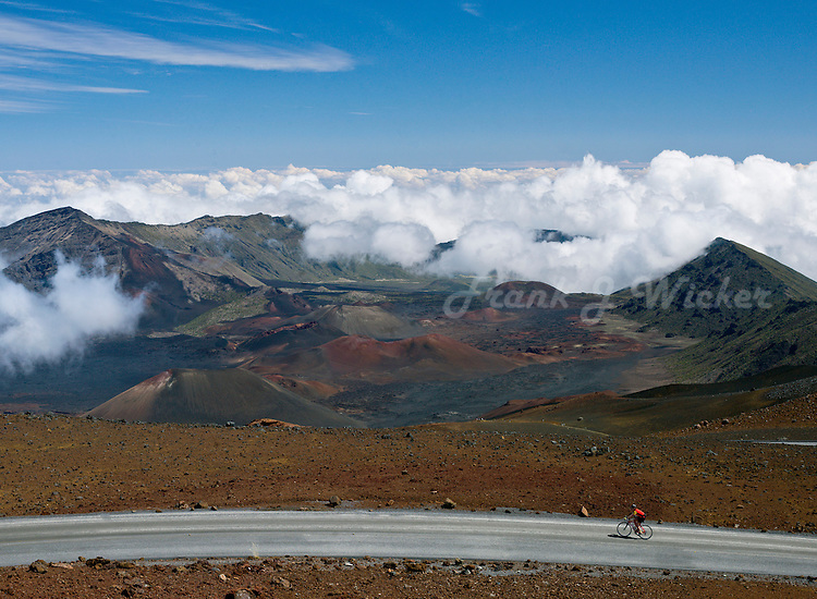 Lone bike rider on the road in HALEAKALA NATIONAL PARK high above the clouds on Maui in Hawaii USA